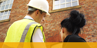 A woman in business clothes speaking to a construction manager in front of a building